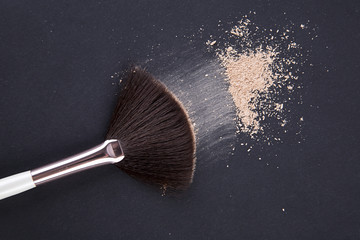 makeup brush and powder on the black background