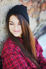 Young long-haired brunette girl sitting near brick wall and smiling sweetly, shyly lowering his eyes, close up.