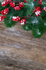 red and white christmas - twig with red berries and green evergreen tree on wooden background with copy space