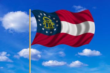 Flag of Georgia state waving on blue sky backdrop