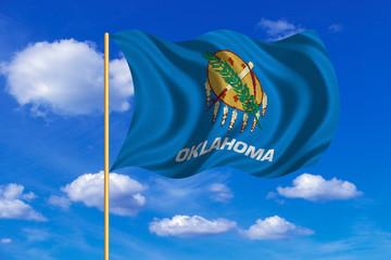Flag of Oklahoma waving on blue sky background