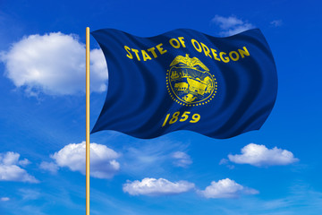 Flag of Oregon waving on blue sky background