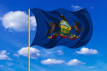Flag of Pennsylvania waving on blue sky background