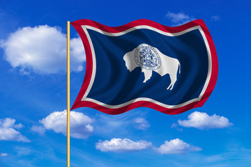Flag of Wyoming waving on blue sky background