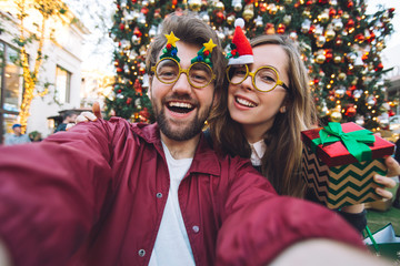 Happy couple in with decorated bags making selfie near Christmas tree in a mall when shopping. Concept happy celebration of Christmas and New Year holidays.