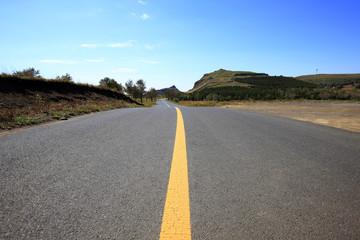 asphalt road on grassland
