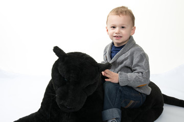Little boy playing with a panther soft toy
