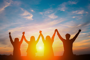 Silhouette of happy business team making high hands in sunset sky