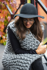 the beautiful girl in warm knitted clothes, in a hat and transparent glasses, is heated, fall