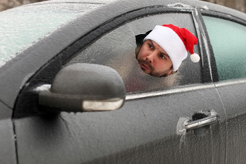 man in a red cap of Santa Claus in a car with broken glass