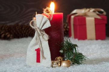 Erster Advent-Rote Adventskerze im Schnee mit goldenen Kugeln, G