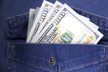 Several hundred us dollar banknotes stuck out blue jeans pocket.