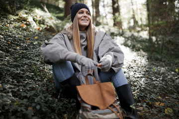 Young stylish female sitting in forest