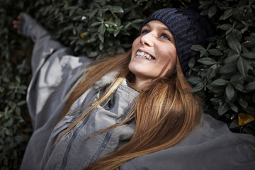 Woman in warm clothing lying on ground