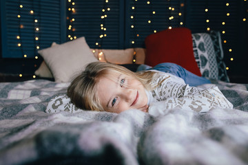 cute little girl in a sweater on the bed on a winter day