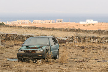 Destroyed car out in the country against the sea.