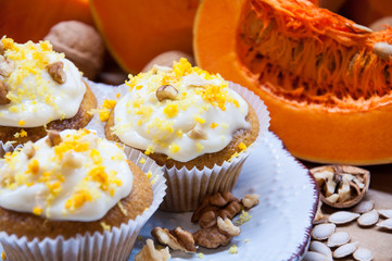 pumpkin cupcakes with cream and pumpkin on a table