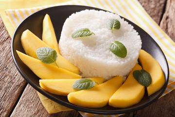 Glutinous rice with ripe mango close-up te on the table. Horizontal