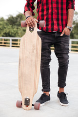 Cropped photo of young dark skinned guy holding his skateboard