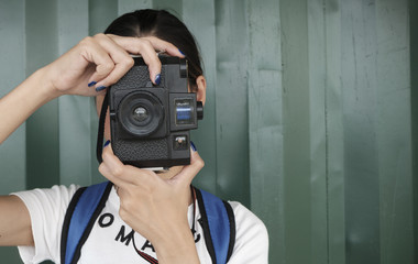 young woman using analog film camera, travel concept