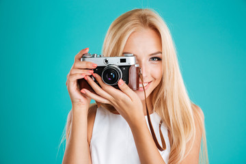 Smiling blonde woman taking photo with retro camera