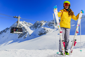 Smiling girl standing with ski and arms spreading wide open on t