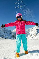 Happy child girl having fun, playing with snow at winter ski res