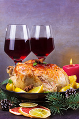 Festive Christmas turkey baked with orange, lemon and lime. Glasses of red wine and candles