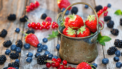 Fresh berries - antic pail full with strawberries. Selective foc