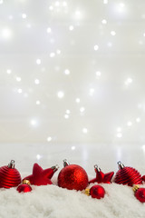 Christmas scene with snow - row of red balls with bokeh lights in background