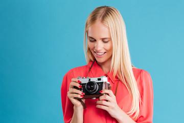 Portrait of a pretty casual blonde girl with retro camera