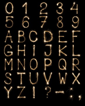 English Letters from sparklers, alphabet and numbers on black background.