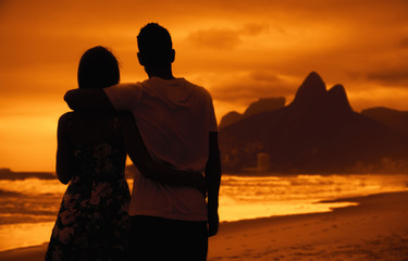 Love couple in arms on beach at sunset at Rio de Janeiro