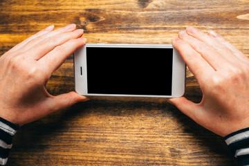 Woman using smart phone in horizontal landscape orientation