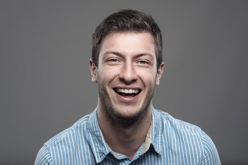 Close up moody horizontal portrait of young successful man laughing and looking at camera