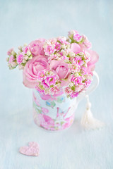 Lovely bunch of a pink flowers in a vase ,decorated with a heart on a table .Vintage style ,grunge paper background.
