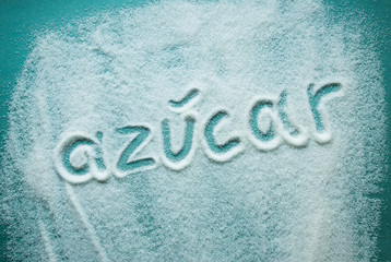 word sugar written in Spanish into a pile of white granulated sugar