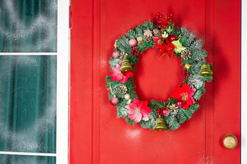 Christmas wreath with baubles, cones and evergreen boughs on a red door. Texture and background. Christmas card