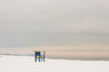 Lifeguard tower at the snowy beach with pink clouds, Ventspils, Baltic sea