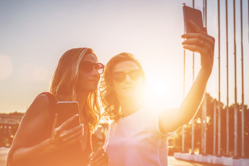 Summer sunny day, backlight, two smiling young women in sunglasses with blond hair standing outside and take pictures on your smartphone. Girls using a digital gadgets. Film effect.Instagram filter.