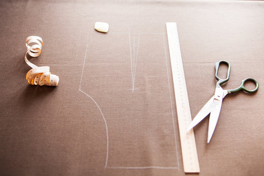 Still life photo of a suit pattern template with tape measure, c