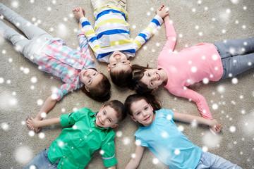 happy smiling children lying on floor over snow