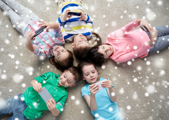 happy children with smartphones lying on floor