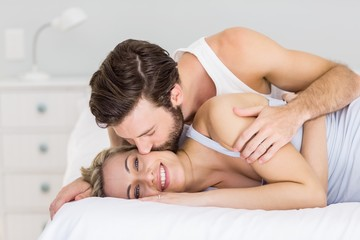 Romantic couple embracing on bed