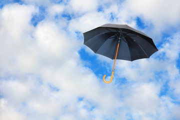 Mary Poppins umbrella.Black umbrella flies in sky against of pure white clouds.Wind of change concept.