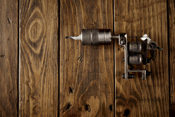 Crome steel handmade traditional induction tattoo gun on rustic wooden table top view