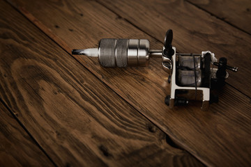 Crome steel handmade traditional professional induction tattoo gun isolated on rustic wooden table, side view