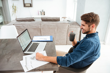 Cheerful young man drinking coffee while sitting near laptop