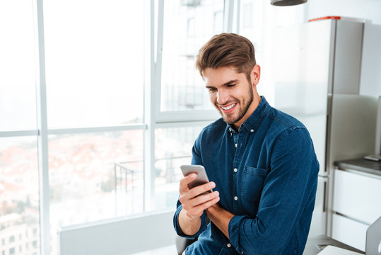 Young man using a smartphone and smiling indoors