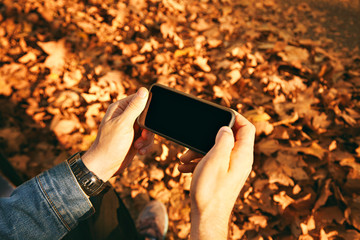 Smartphone with blank screen held by hands of a man in denim jacket against sunlit autumn leaves background